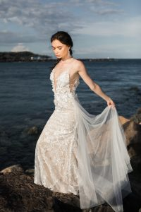 woman-wearing-white-floral-wedding-dress-standing-on-rocks-2122363